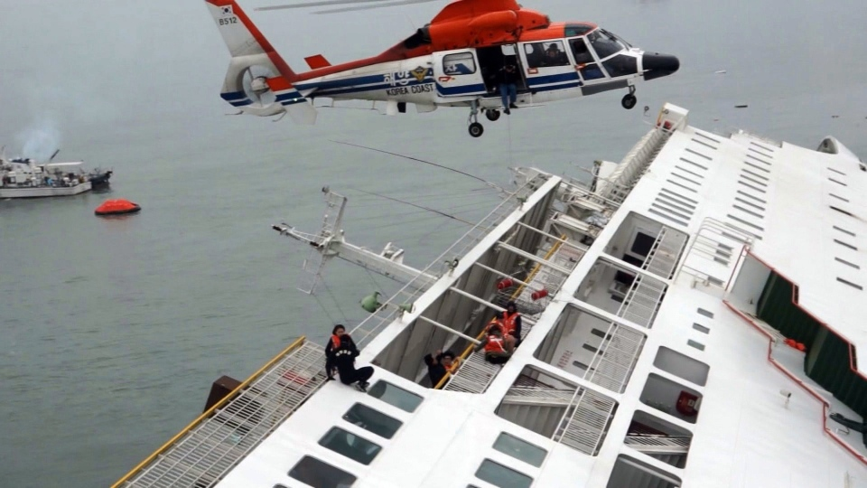Passengers from a ferry sinking off South Korea's southern coast, are rescued by a South Korean Coast Guard helicopter in the water off the southern coast near Jindo, south of Seoul, Wednesday, April 16, 2014. (Yonhap)
