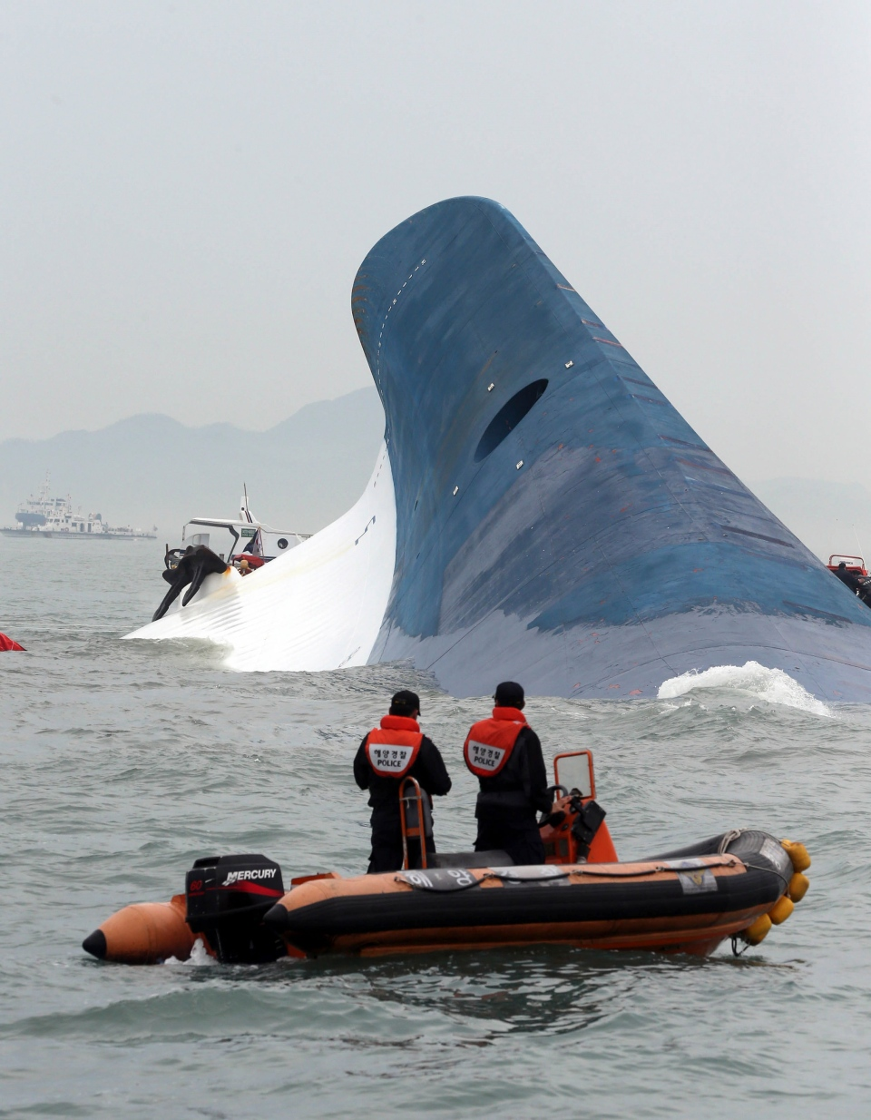 South Korean coast guard officers try to rescue passengers from ferry Sewol in the water off the southern coast near Jindo, south of Seoul, South Korea, Wednesday, April 16, 2014. (Hyung Min-woo / Yonhap)