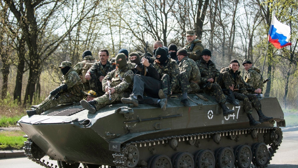 A combat vehicle with a Russian flag makes its way to the town of Kramatorsk on Wednesday, April 16, 2014. (AP / Evgeniy Maloletka)