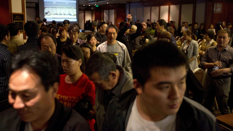 Relatives of Chinese passengers onboard the missing Malaysia Airlines 370 walk out from a video-conference with Malaysian officials in protest at the difficulties of communications in Beijing, China, Wednesday, April 16, 2014. (AP / Ng Han Guan)
