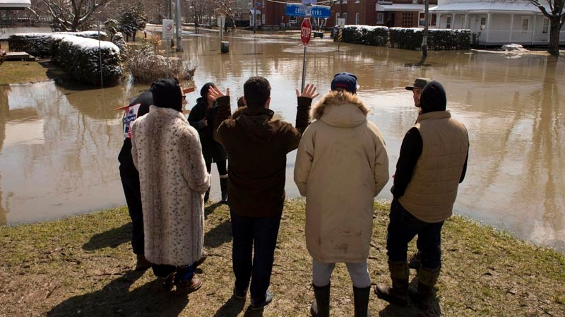 People look at a flooded street as the St. Francois river overflows its banks Wednesday, April 16, 2014 in Lennoxville, Quebec. THE CANADIAN PRESS/Ryan Remiorz