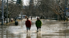 People walk through a flooded street as the St. Fr
