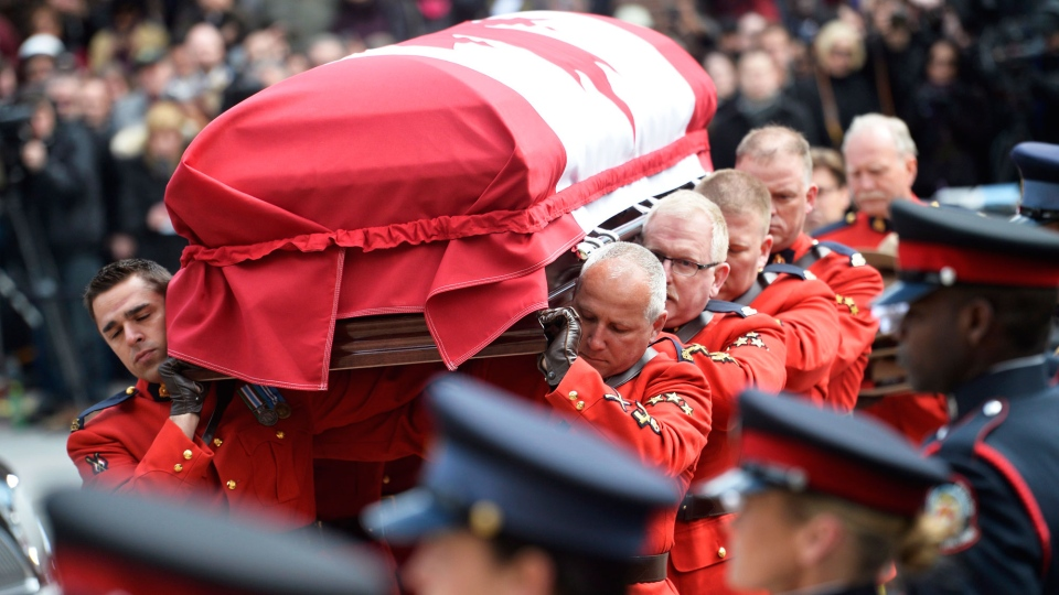 The casket carried by RCMP members carrying the late Jim Flaherty arrives at the church for the state funeral in Toronto on Wednesday, April 16, 2014. (Nathan Denette / THE CANADIAN PRESS)