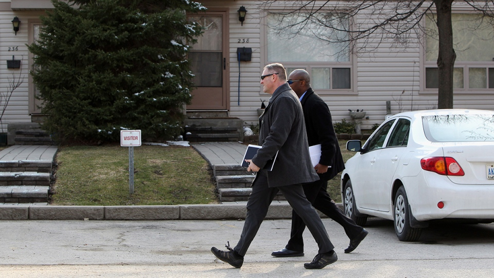RCMP investigators walk past the house of Stephen Arthuro Solis-Reyes, 19, in London, Ont., Wednesday, Apr. 16, 2014. (Dave Chidley / THE CANADIAN PRESS)