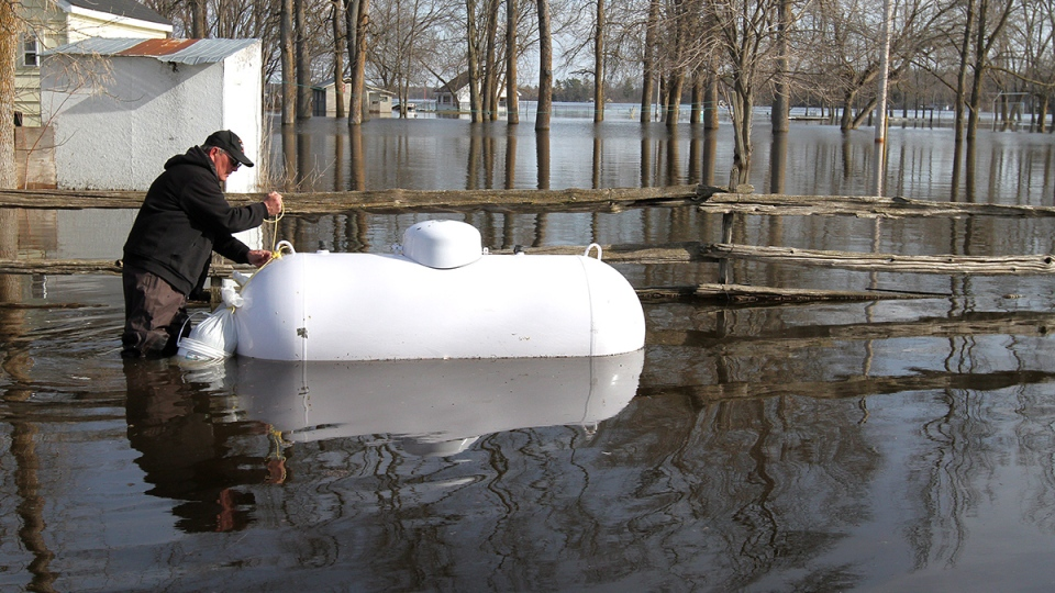 Leonard Gray anchors his propane tank in his backyard in Tweed, Ont., north of Belleville, on Wednesday, April 16, 2014. (Lars Hagberg / THE CANADIAN PRESS)
