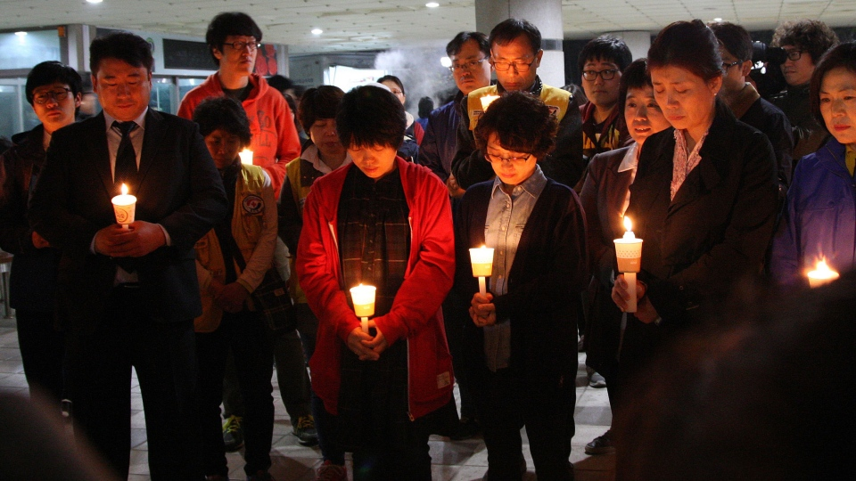 Parents attend a candle light vigil to hope for their children's safe return at Danwon high school in Ansan, South Korea, Wednesday, April 16, 2014. (Yonhap)