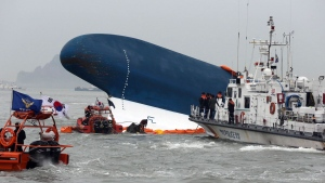 South Korean Coast Guard officers try to rescue missing passengers from a sunken ferry in the water off the southern coast near Jindo, south of Seoul, South Korea, Thursday, April 17, 2014. (Yonhap)