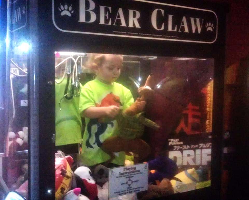 In this photo provided by Rachelle Hildreth, a 3-year-old boy plays with stuffed toys inside a claw crane game machine at a bowling alley in Lincoln, Neb. (AP / Courtesy Rachell Hildreth)