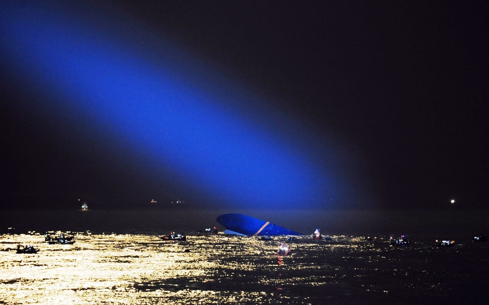 Blue search light cast by South Korean Coast Guard helicopter shows a sunken ferry in the water off the southern coast near Jindo, South Korea, Thursday, April 17, 2014. (Yonhap)