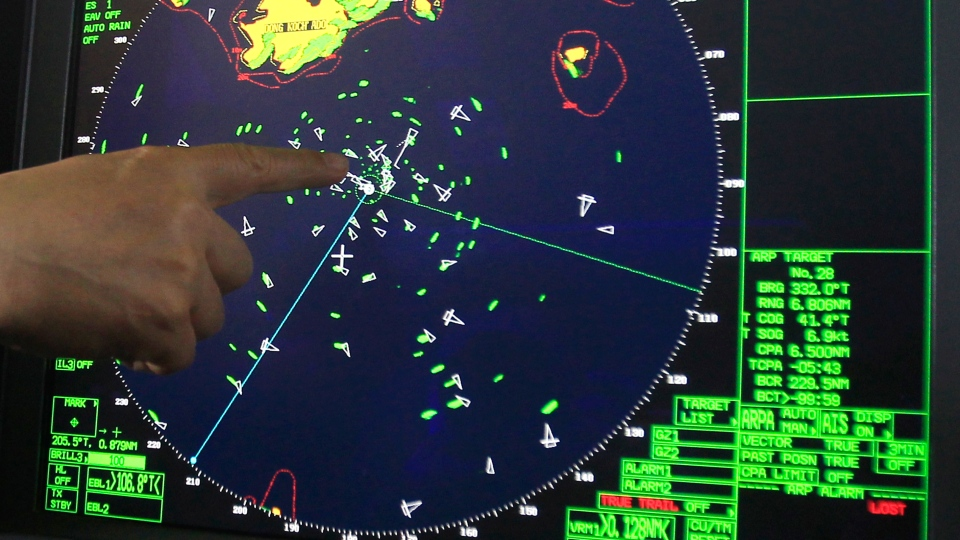 An official on a South Korean Coast Guard ship points out a radar displaying the area a sunken ferry in the water off the southern coast near Jindo, Thursday, April 17, 2014. (AP / Ahn Young-joon)