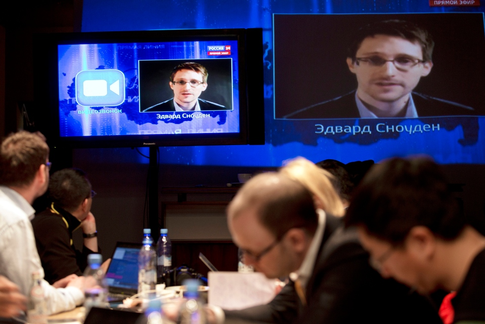 Edward Snowden, seen on television screens, asks a question to Russian President Vladimir Putin during a nationally televised question-and-answer session, in Moscow on Thursday, April 17, 2014.  (AP / Pavel Golovkin)