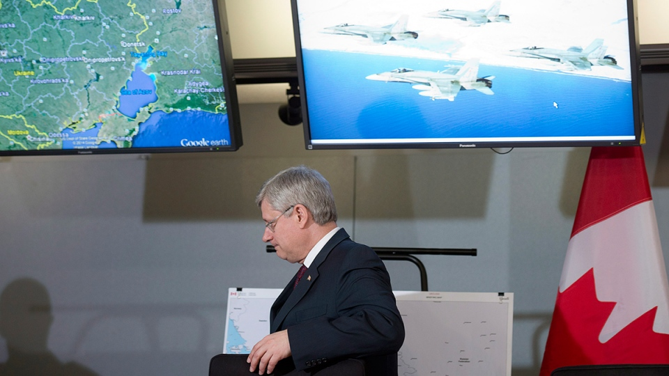 Prime Minister Stephen Harper leaves a secure briefing room after announcing Canada will send six CF-18 fighter jets to eastern Europe as part of a NATO mission, in Ottawa, Thursday, April 17, 2014. (Adrian Wyld / THE CANADIAN PRESS)