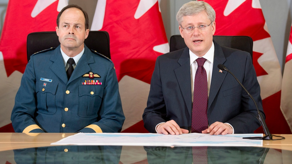 Prime Minister Stephen Harper and Chief of Defence Staff General Thomas Lawson announces Canada will send six CF-18 fighter jets to eastern Europe as part of a NATO mission during a press conference in Ottawa on Thursday, April 17, 2014. (Adrian Wyld / THE CANADIAN PRESS)