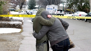Women cry and hug beside a makeshift memorial near the scene of the multiple fatal stabbings in northwest Calgary on Wednesday, April 16, 2014. (Larry MacDougal / THE CANADIAN PRESS)