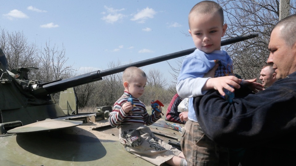 Local residents look at the airborne combat vehicle destroyed during a Ukrainian night combat operation in the village of Horodychevo, near Kramatorsk, Ukraine, Friday, April 18, 2014. (AP / Efrem Lukatsky)