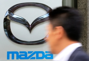 A man walks in front of Mazda's logo at its showroom in Tokyo, Wednesday, Oct. 31, 2012. (AP Photo/Shizuo Kambayashi)