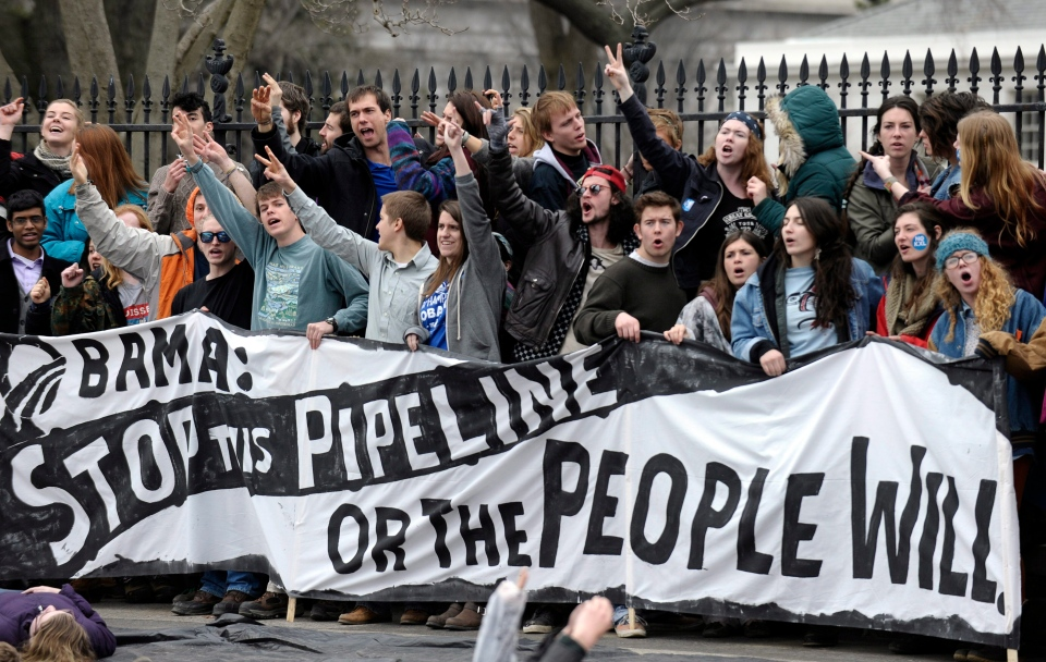 Several hundred students and youth who marched from Georgetown University to the White House to protest the Keystone XL Pipeline yell as they wait to be arrested outside the White House in Washington, Sunday, March 2, 2014. (AP / Susan Walsh)