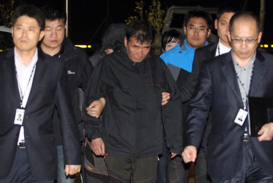 Lee Joon-seok, center, the captain of the sunken ferry Sewol in the water off the southern coast, arrives at a court which issues his arrest warrant in Mokpo, south of Seoul, South Korea, Friday, April 18, 2014. (AP / Yonhap)