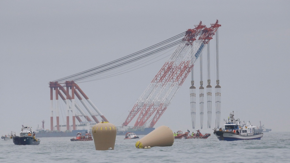 Cranes wait near the buoys installed to mark the sunken ferry Sewol in the water off the southern coast near Jindo, South Korea, Friday, April 18, 2014. (AP / Lee Jin-man)