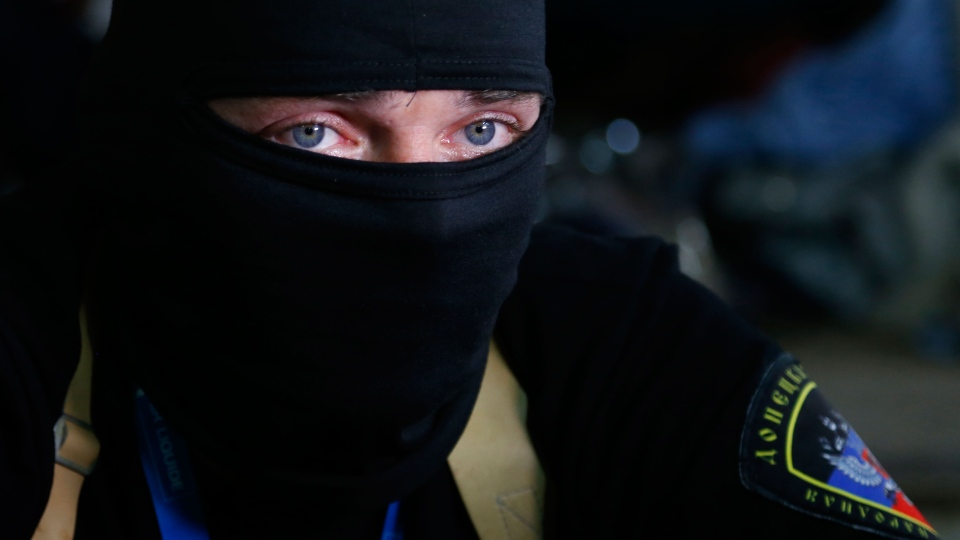 A masked pro-Russian activist guard looks through a window of the regional administration building seized earlier in Donetsk, Ukraine, Friday, April 18, 2014. (AP / Sergei Grits)