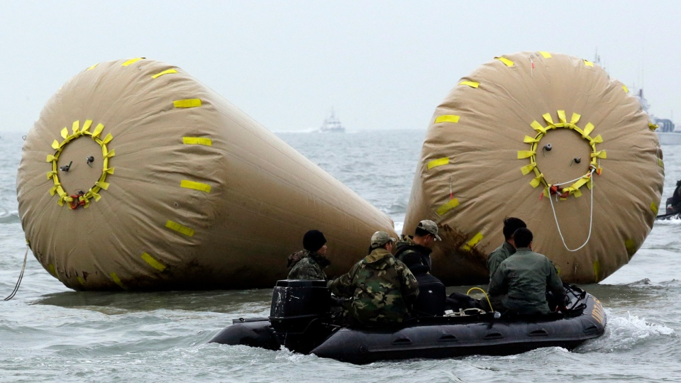 South Korean navy personnel on boats search passengers of the sunken ferry Sewol near buoys which were installed to mark the area in the water off the southern coast near Jindo, south of Seoul, South Korea, Saturday, April 19, 2014. (AP / Lee Jin-man)