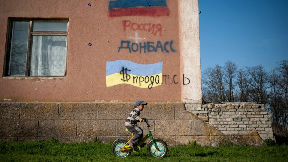 A boy rides a bicycle past a building with Russian and Ukrainian national flags in Uspenka village in Ukraine's Donbas region, four kilometres from the Ukrainian-Russian border, on Friday, April 18, 2014. (AP / Evgeniy Maloletka)