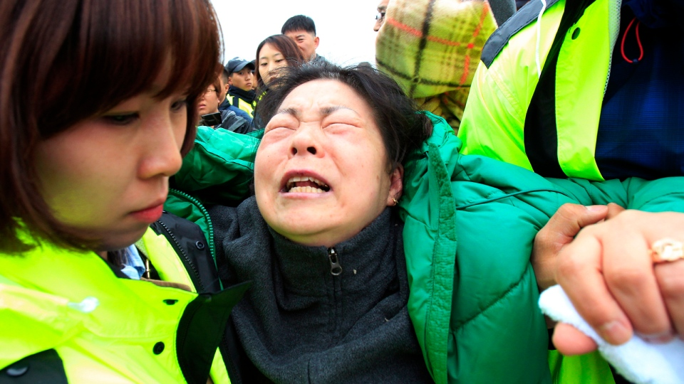 A relative of a passenger aboard the sunken ferry Sewol in the water off the southern coast, weeps as she waits for her missing loved one at a port in Jindo, South Korea, Saturday, April 19, 2014. (AP / Ahn Young-joon)