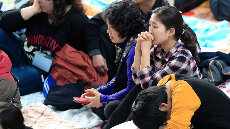 Relatives of missing passengers aboard the sunken ferry Sewol in the water off the southern coast listen to a briefing from Korea Coast Guard officials about a rescue and search operation, at a gymnasium in Jindo, South Korea, Saturday, April 19, 2014. (AP / Ahn Young-joon)