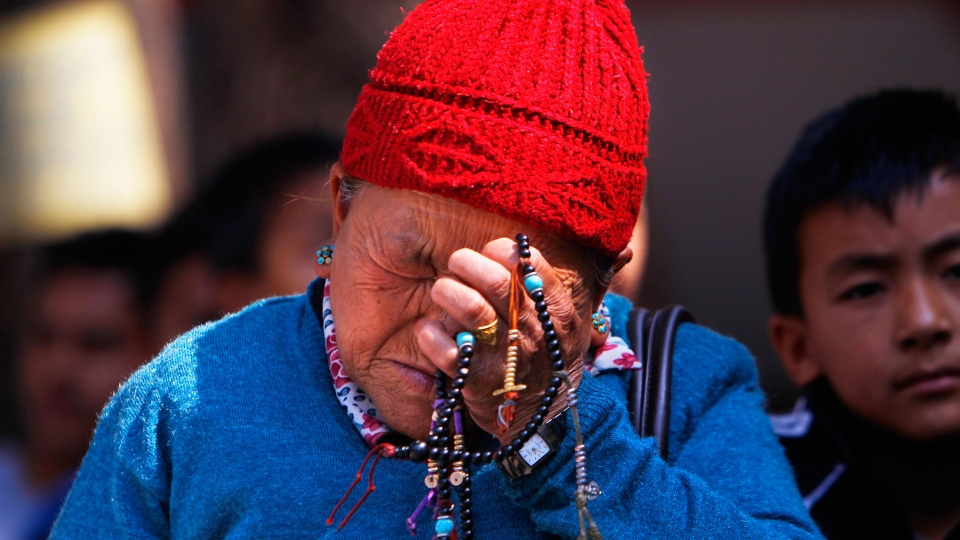 Mother of Nepalese mountaineer Ang Kaji Sherpa, killed in an avalanche on Mount Everest, holds prayers beads in her hand and cries while she waits for his body at Sherpa Monastery in Katmandu, Nepal, Saturday, April 19, 2014. (AP / Niranjan Shrestha)