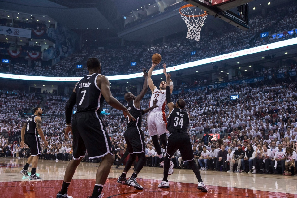 Toronto Raptors' Jonas Valanciunas (centre) shoots on the Brooklyn Nets' defence during first half NBA playoff basketball action in Toronto on Saturday April 19, 2014. (Chris Young /  THE CANADIAN PRESS)