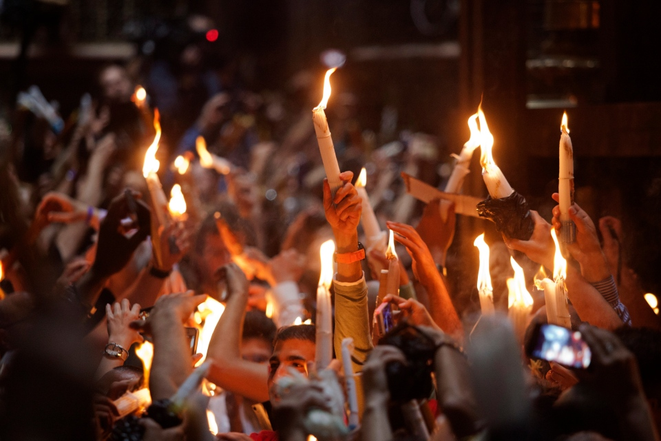 Christian pilgrims hold candles at the church of the Holy Sepulcher, traditionally believed to be the burial site of Jesus Christ, during the ceremony of the Holy Fire in Jerusalem's Old City, Saturday, April 19, 2014. (AP / Dan Balilty)