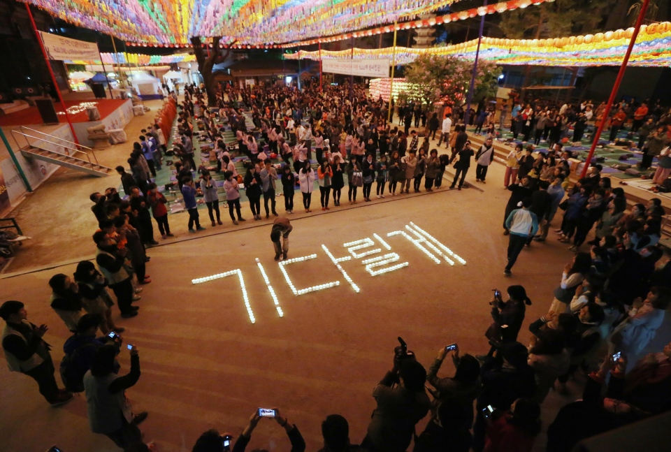 Buddhists hold a service to wish for safe return of missing passengers aboard the sunken ferry Sewol, at Jogye temple in Seoul, South Korea, Saturday, April 19, 2014. The candles form Korean letters which mean 'Waiting.' (Yonhap, Park Dong-joo)