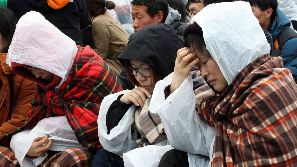Relatives of missing passengers aboard the sunken ferry Sewol sit on the road as they try to march toward the presidential house to protest the government's rescue operation at a port in Jindo, South Korea, Sunday, April 20, 2014. (AP / Ahn Young-joon)