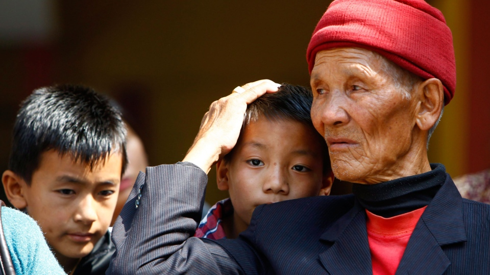 Father and sons of Nepalese mountaineer Ang Kaji Sherpa, killed in an avalanche on Mount Everest, wait for his body to arrive at Sherpa Monastery in Katmandu, Nepal, Saturday, April 19, 2014. (AP / Niranjan Shrestha)
