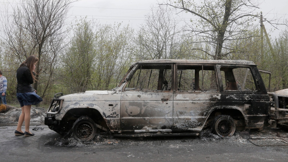 Local residents inspect burnt out cars after a night fight at the check point which was under the control of pro-Russian activists in the village of Bulbasika near Slovyansk, Ukraine, Sunday, April 20, 2014. (AP / Efrem Lukatsky)
