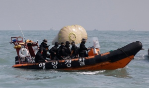 South Korean rescue team members on a boat sail to rescue missing passengers believed to have been trapped in the sunken ferry Sewol near the buoys which were installed to mark the vessel in the water off the southern coast near Jindo, south of Seoul, South Korea, Sunday, April 20, 2014. After more than three days of frustration and failure, divers on Sunday finally found a way into the submerged ferry off South Korea's southern shore, discovering more than a dozen bodies inside the ship and pushing the confirmed death toll to over four dozen, officials said. (AP Photo/Lee Jin-man)