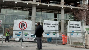 A man stands at the locked gates at the site of the new French superhospital as construction workers walked off the job for the second day in a row Tuesday, October 25, 2011 in Montreal.THE CANADIAN PRESS/Ryan Remiorz