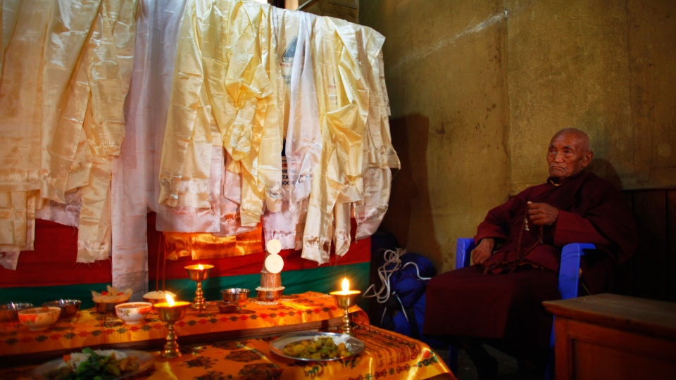 A Buddhist monk performs rituals next to a casket containing the dead body of Nepalese mountaineer Ang Kaji Sherpa, killed in an avalanche on Mount Everest, offer prayers at the Sherpa Monastery in Katmandu, Nepal, Sunday, April 20, 2014. (AP / Niranjan Shrestha)
