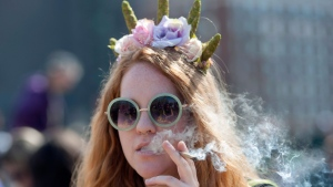 A woman smokes a joint at the Fill the Hill marijuana rally on Parliament Hill in Ottawa on Sunday, April 20, 2014. (Justin Tang / THE CANADIAN PRESS)