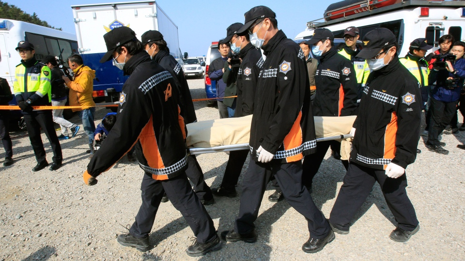 The body of a passenger aboard the Sewol ferry which sank in the water off the southern coast, is carried by rescue workers upon its arrival at a port in Jindo, South Korea, Monday, April 21, 2014. (AP / Ahn Young-joon)
