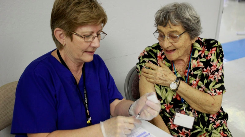 Angela Hapgood, right, gets her flu shot at a flu clinic at the Manzanita Senior Center as part of the Influenza Immunization for You initiative, which aims to inform seniors about the importance of vaccination and the vaccine options for adults 65 years of age and older on Tuesday, Sept. 27, 2011, in Phoenix, Ariz.