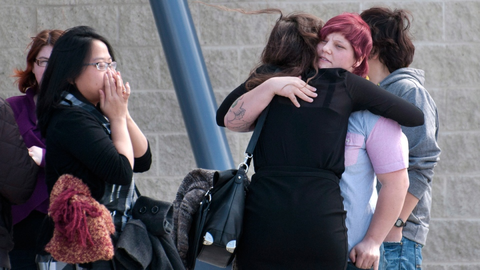 People hug as they arrive at a memorial service for Lawrence Hong, victim of April 15th mass stabbing, in Calgary, on Sunday, April 20, 2014. (Larry MacDougal / THE CANADIAN PRESS)