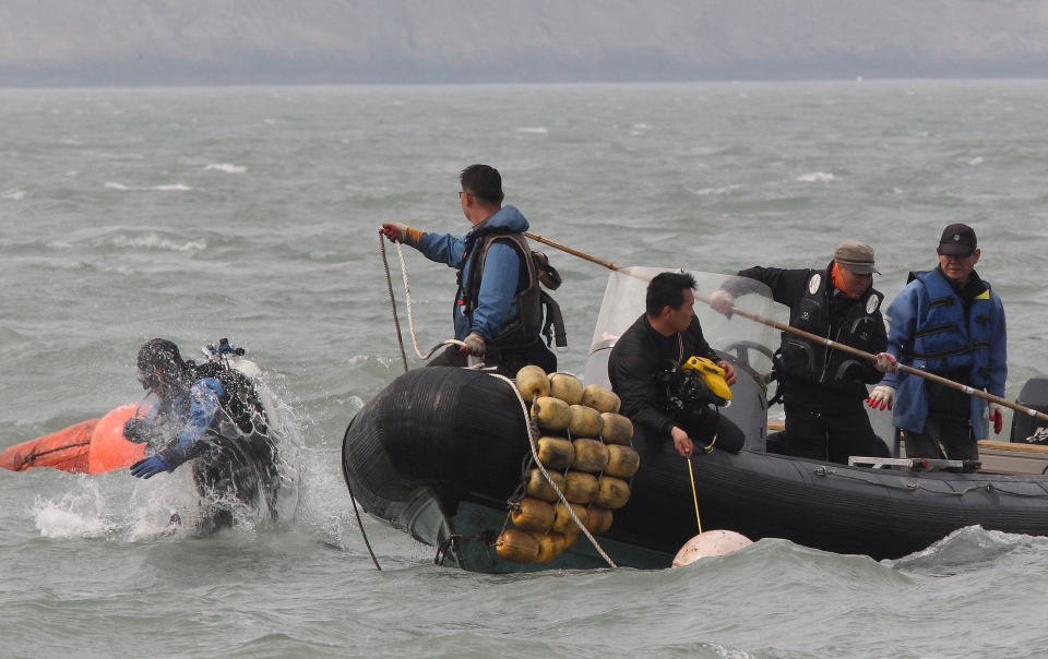 A South Korean frogman dives into a water search passengers believed to have been trapped in the sunken ferry Sewol in the water off the southern coast near Jindo, South Korea, Monday, April 21, 2014. (AP / Ahn Young-joon)