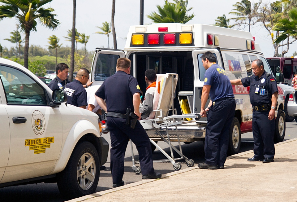 Teen stowaway seen sitting on a stretcher, centre, is loaded into an ambulance at Kahului Airport in Kahului, Maui, Hawaii Sunday afternoon, April 20, 2014. (The Maui News / Chris Sugidono)