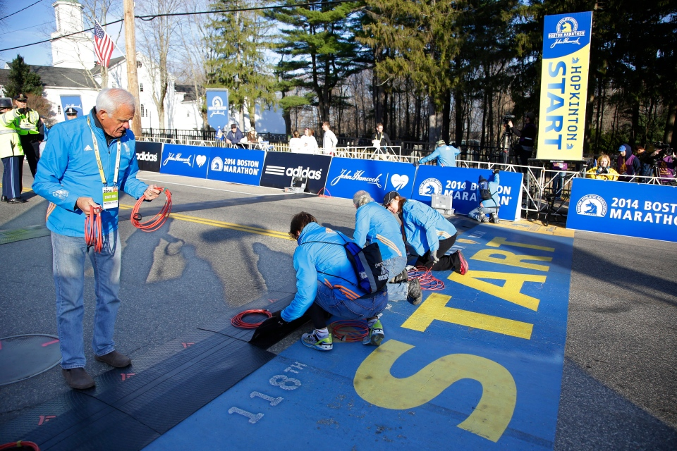 Race officials wire the electronics for the start line before the 118th Boston Marathon begins Monday, April 21, 2014 in Hopkinton, Mass. (AP / Stephan Savoia)