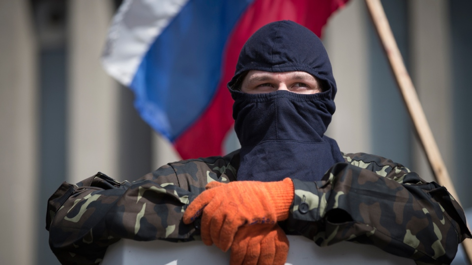 A masked pro-Russia guards barricades as the Russian national flag flies at the Ukrainian regional office of the Security Service in Luhansk, Ukraine, Monday, April 21, 2014. (AP / Alexander Zemlianichenko)