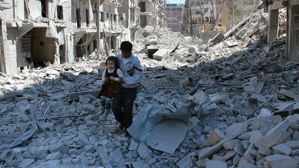 This photo provided by the anti-government activist group Aleppo Media Center (AMC), which has been authenticated based on its contents and other AP reporting, shows a Syrian man holding a girl as he stands on the rubble of houses that were destroyed by Syrian government forces air strikes in Aleppo, Syria, Monday, April 21, 2014. (Aleppo Media Center AMC)