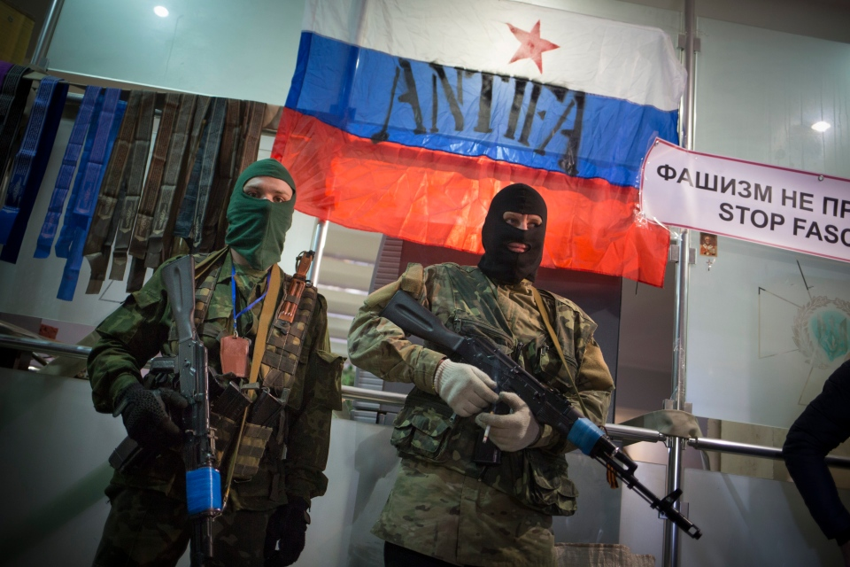 Masked pro-Russian gunmen guard an entrance of the Ukrainian regional office of the Security Service with a Russian National flag is in background in Luhansk, Ukraine, Monday, April 21, 2014. (AP / Alexander Zemlianichenko)