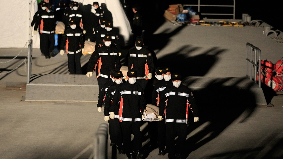 The bodies of a passengers aboard the Sewol ferry which sank in the water off the southern coast, are carried by rescue workers upon its arrival at a port in Jindo, South Korea, Monday, April 21, 2014. (AP / Ahn Young-joon)