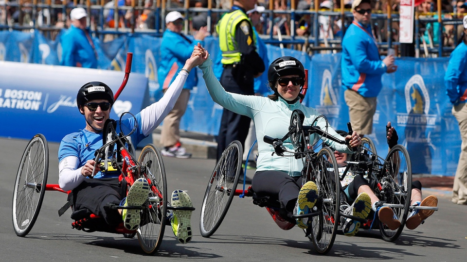 Boston Marathon husband and wife bombing survivors Patrick Downes and Jessica Kensky, who each lost a leg in last year's bombings, roll across the finish line in the 118th Boston Marathon, in Boston, Monday, April 21, 2014. (AP / Elise Amendola)